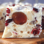 Close of view of side of white Christmas showing pretty ingredients inside, large red cherries, white almonds, cranberries and rice bubbles, set in white chocolate.