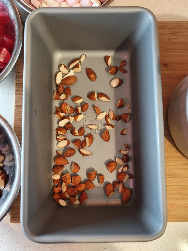 adding first layer of chopped almonds to bottom of chilled ice cream storage container.