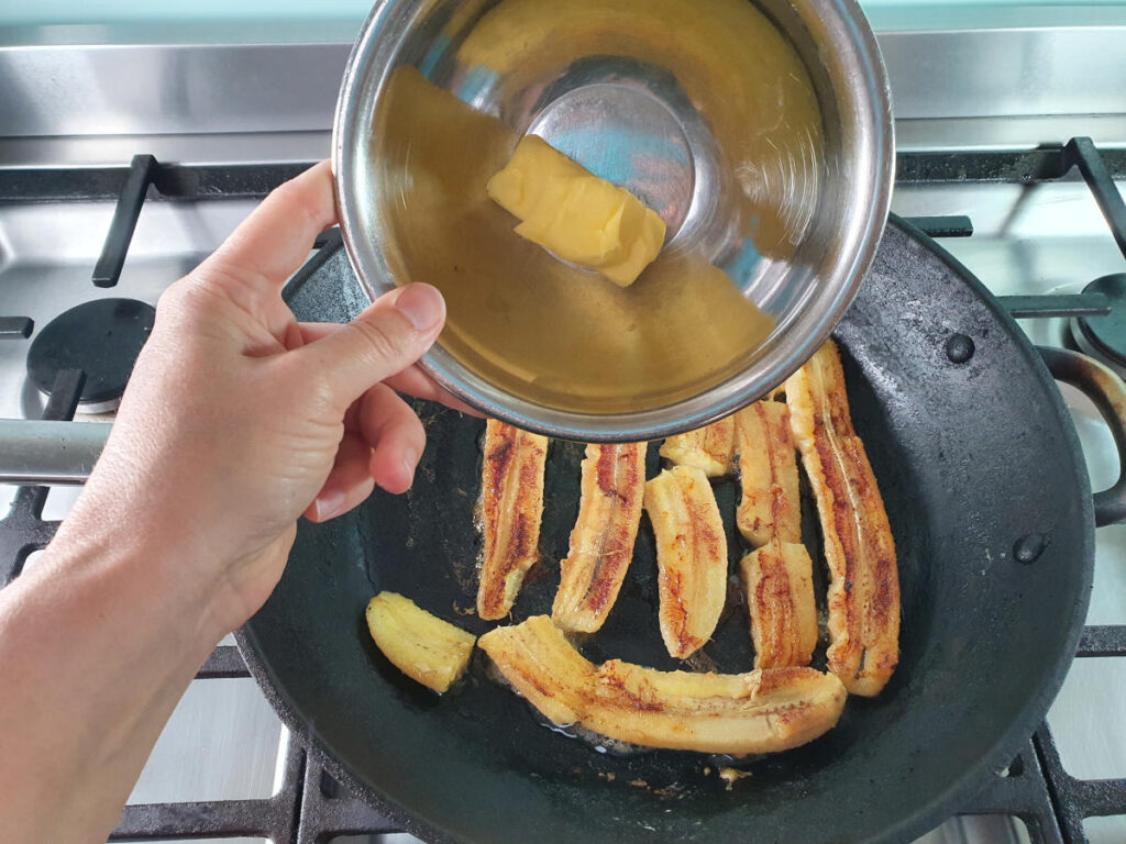 Adding butter to bananas in frying pan on stove.