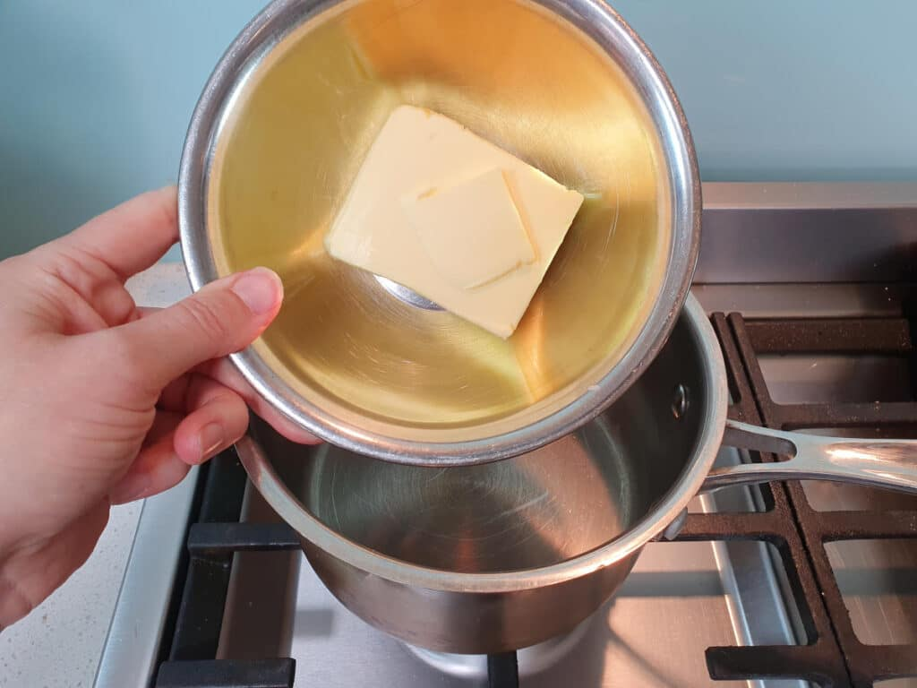 adding butter to pot on stove.