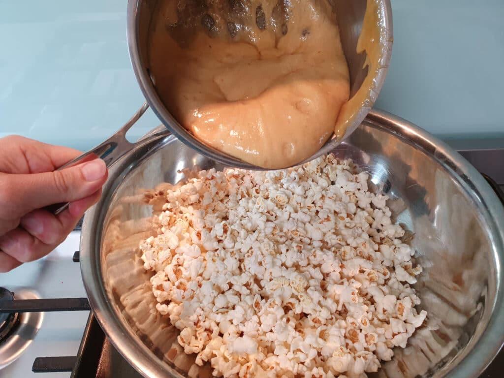 adding caramel to popcorn.