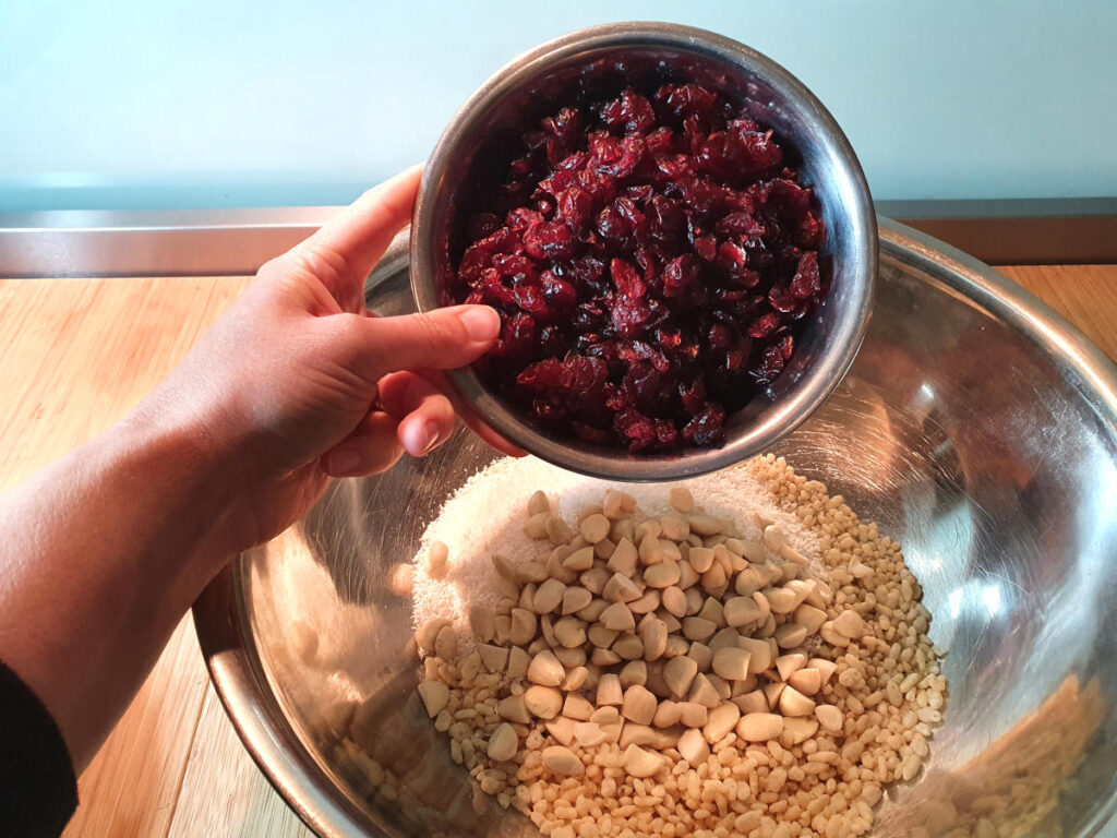 adding dried cranberries to mix in bowl.