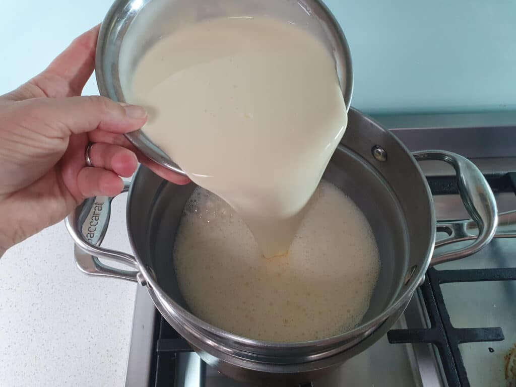 adding cream to ice cream mix in double boiler.