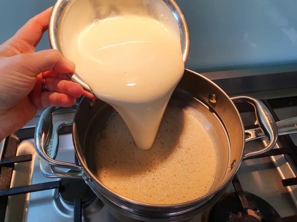 adding cream to ice cream mix in double boiler on stove.