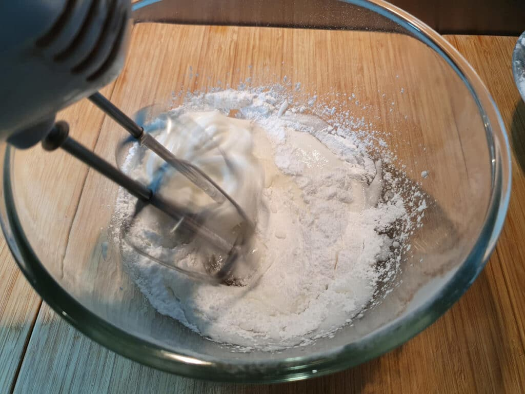 adding icing sugar to egg whites.