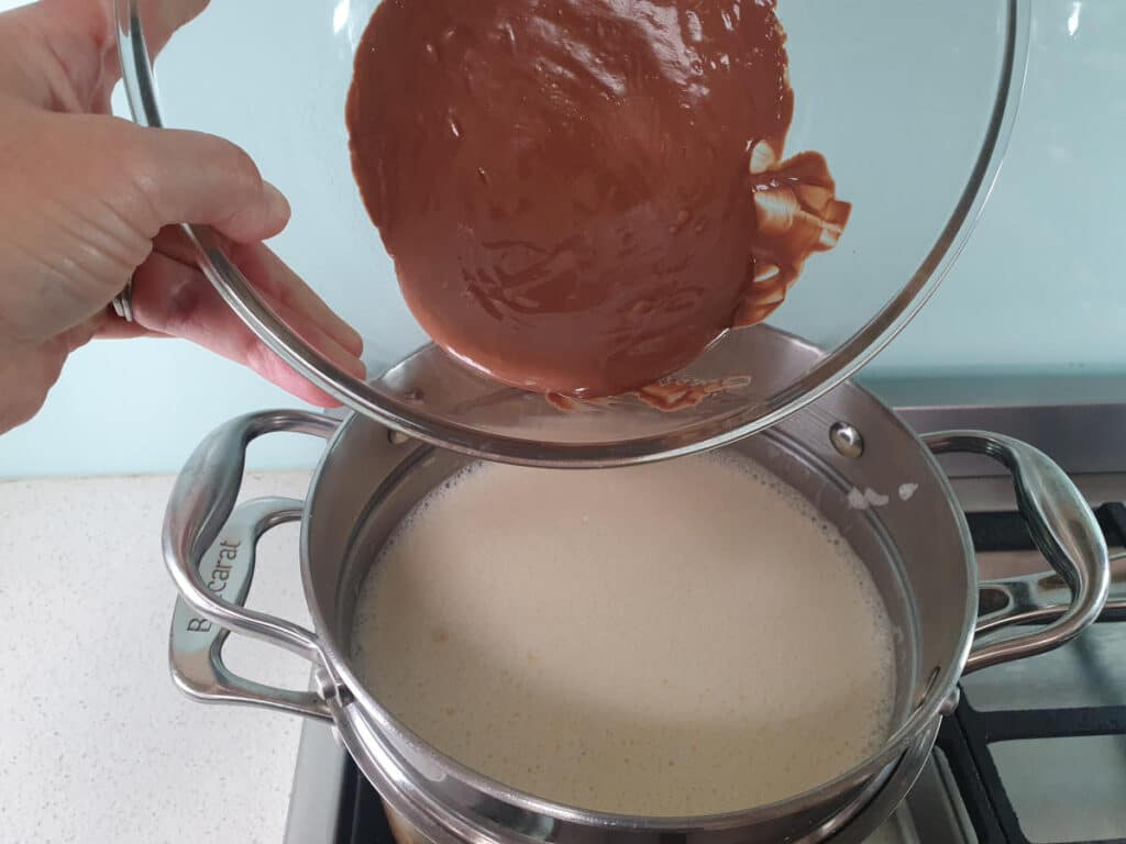 adding melted milk chocolate to ice cream mix in double boiler, about a third at a time.