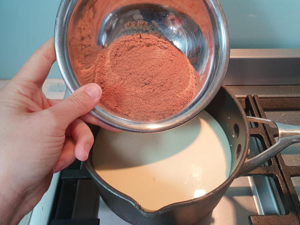 adding milo to ice cream mix in pot.