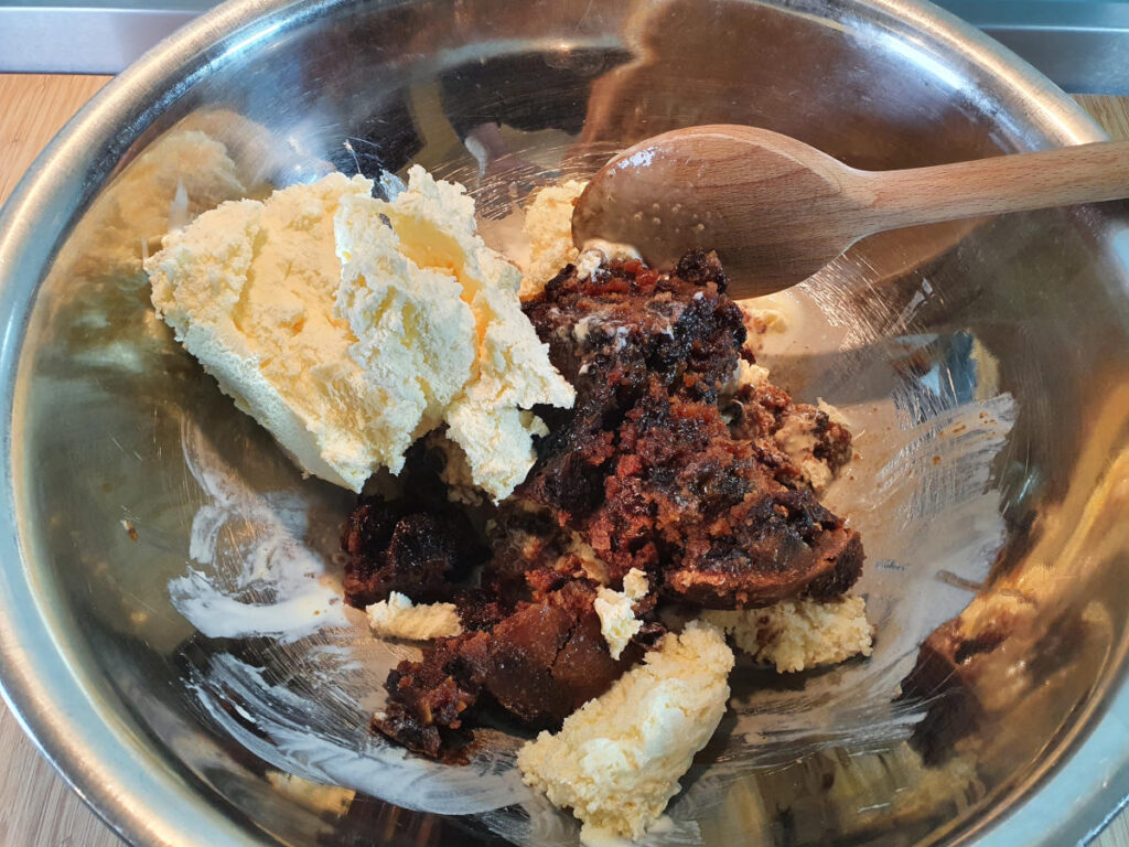 adding more vanilla ice cream to pudding mix in bowl.