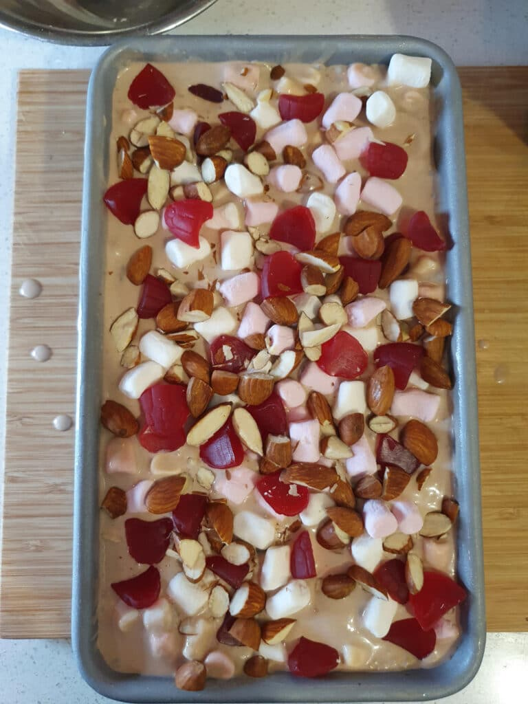 adding top layer of almonds, raspberries and marshmallows to ice cream.