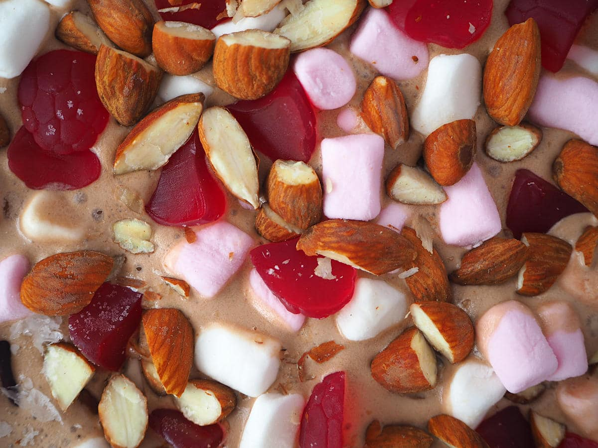 Top down close up view of rocky road ice cream with mini marshmallows, chopped almonds and raspberry candies.