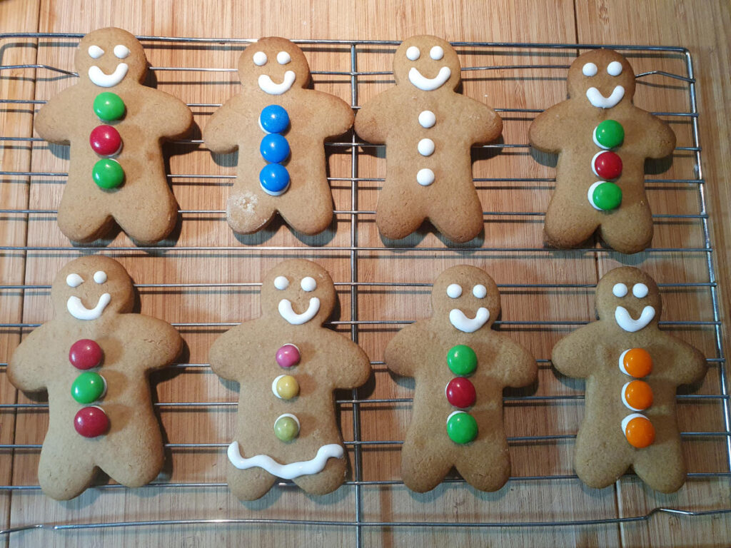 decorated gingerbread men on wire rack drying.