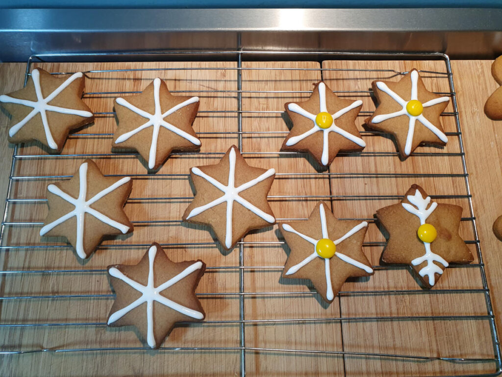 decorated gingerbread stars on wire rack drying.