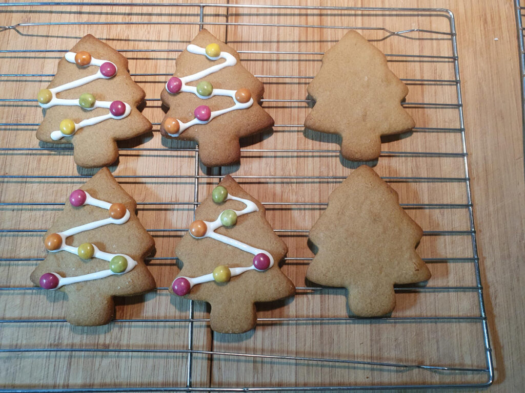 decorated gingerbread Christmas trees on wire rack drying.