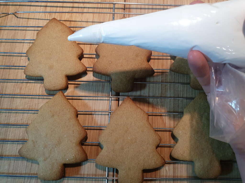 piping icing onto gingerbread trees to decorate.
