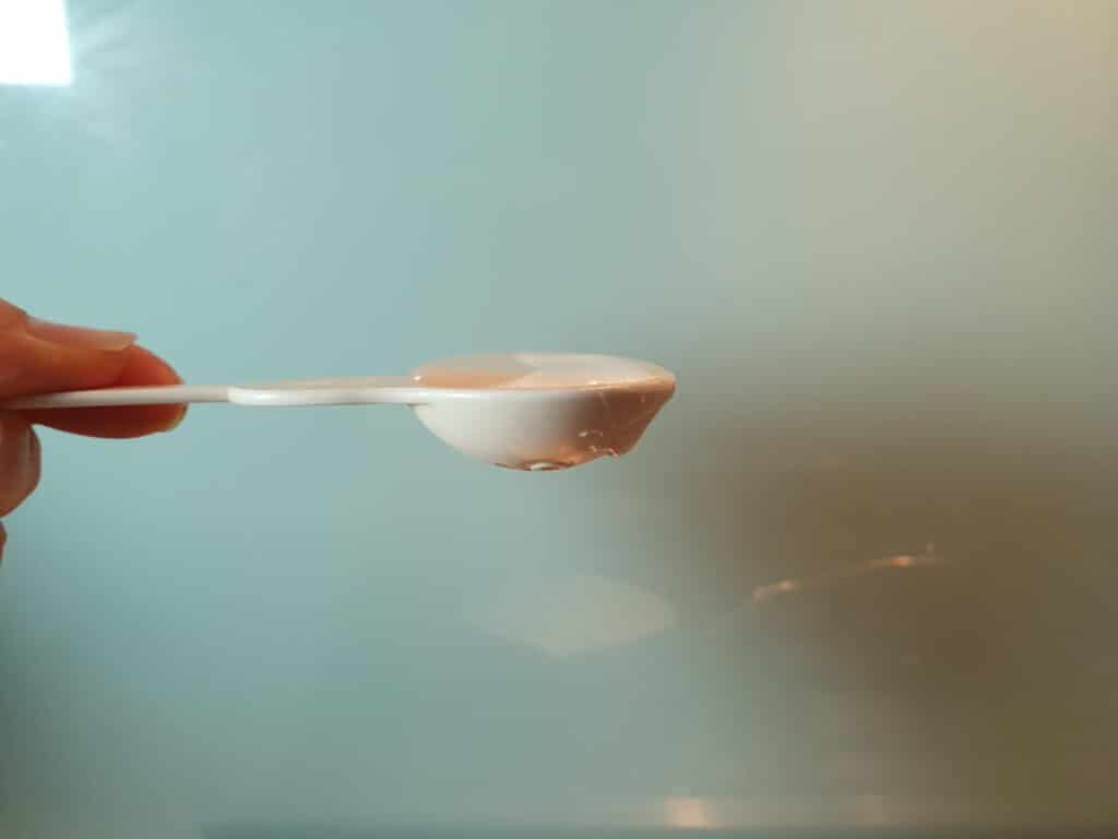 side view of half table spoon measure showing flat table spoon of glucose syrup measured out.