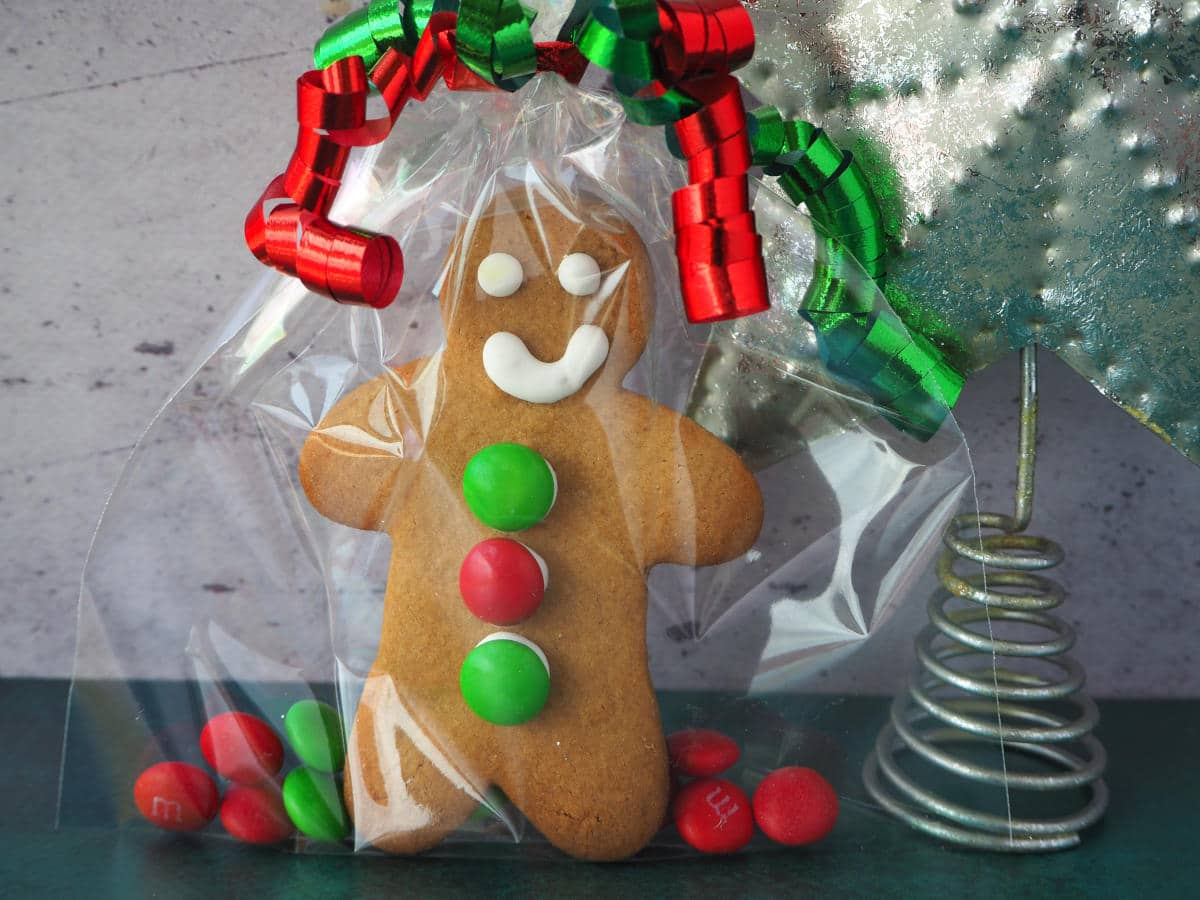 gingerbread man made up as a gift in a clear cellophane bag with red and green M&Ms and green and red curling ribbon around the top, with a silver tree top start to the right.
