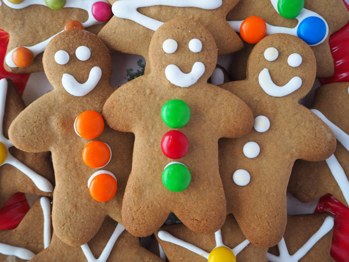 close up of three gingerbread men surrounded by other decorated gingerbread.