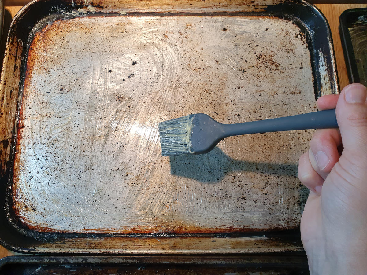 greasing trays with pastry brush and butter.