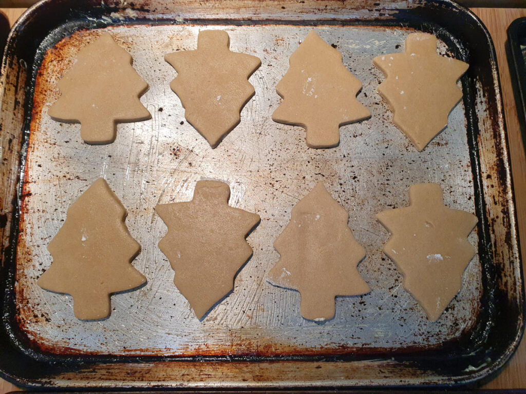 ready to bake christmas tree cookies on a baking tray.