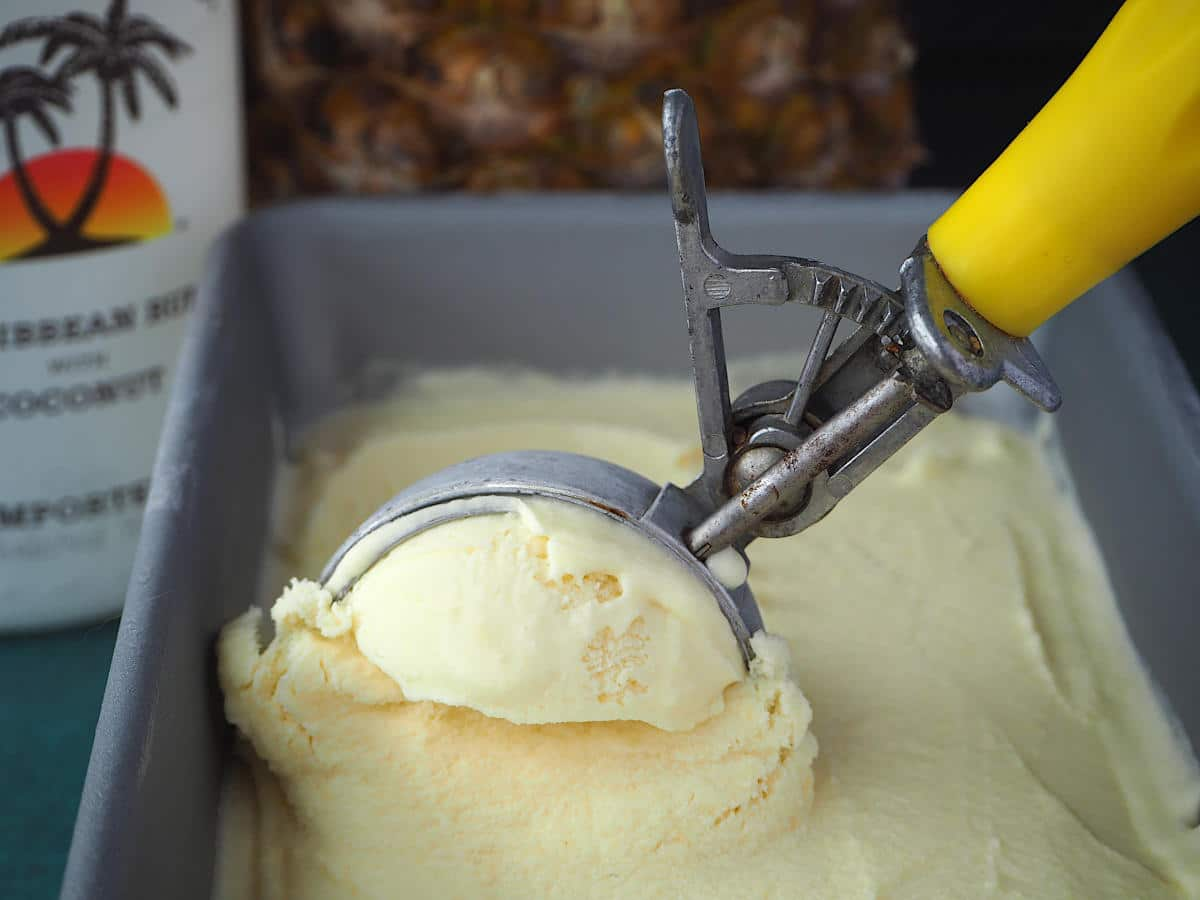 Scooping pina cola ice cream out of a pan with a metal ice cream scoop, with coconut rum and pineapple in the background.