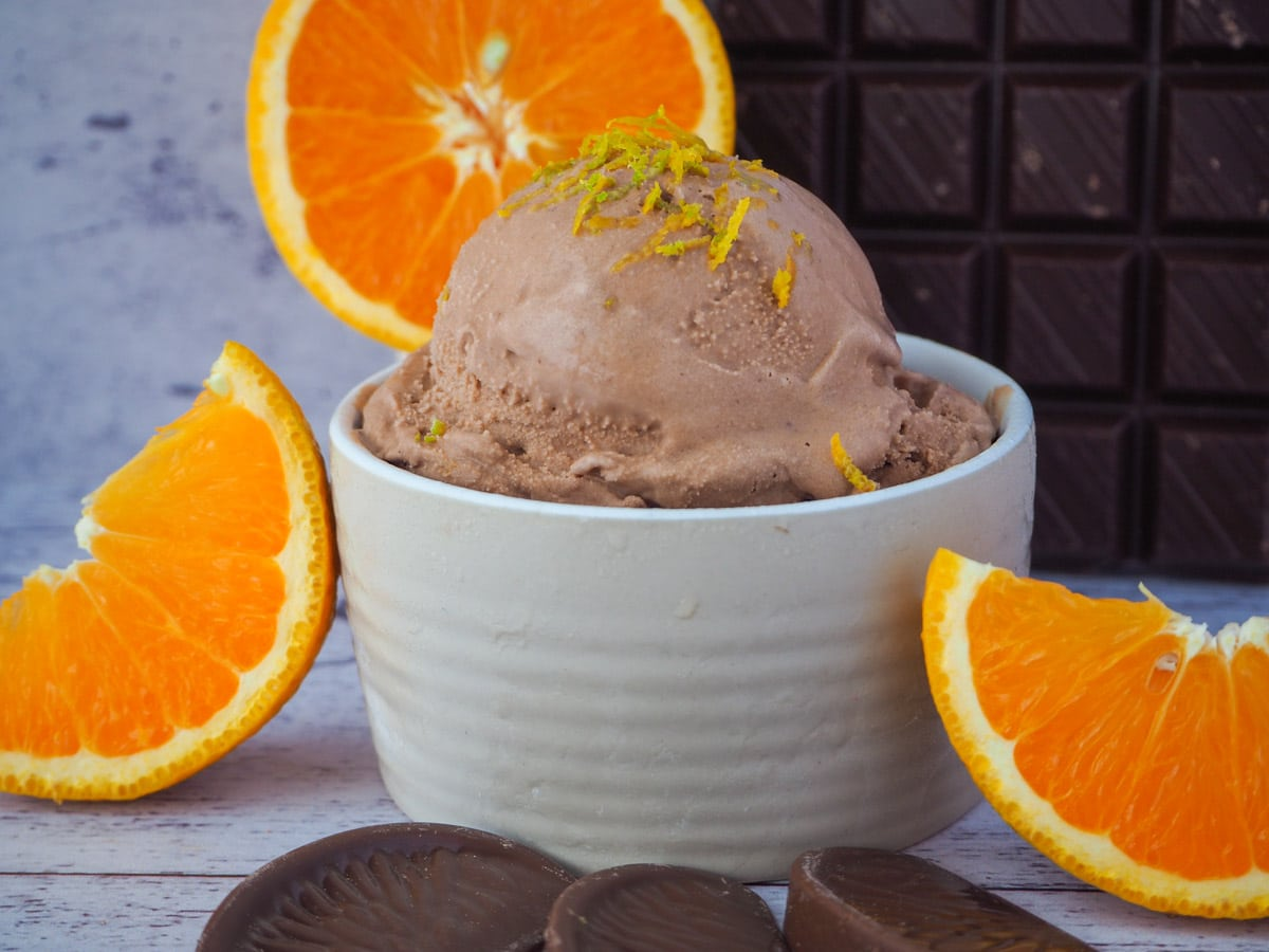 Scoop of chocolate orange ice cream in bowl, with orange zest on top and fresh orange slices in the front and background, and dark chocolate in the background.