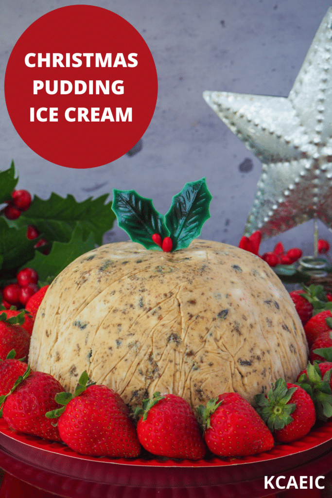Christmas pudding ice cream with holly garnish, surrounded by fresh strawberries, with holly and a Christmas star in the background and text overlay, Christmas pudding ice cream and KCAEIC.