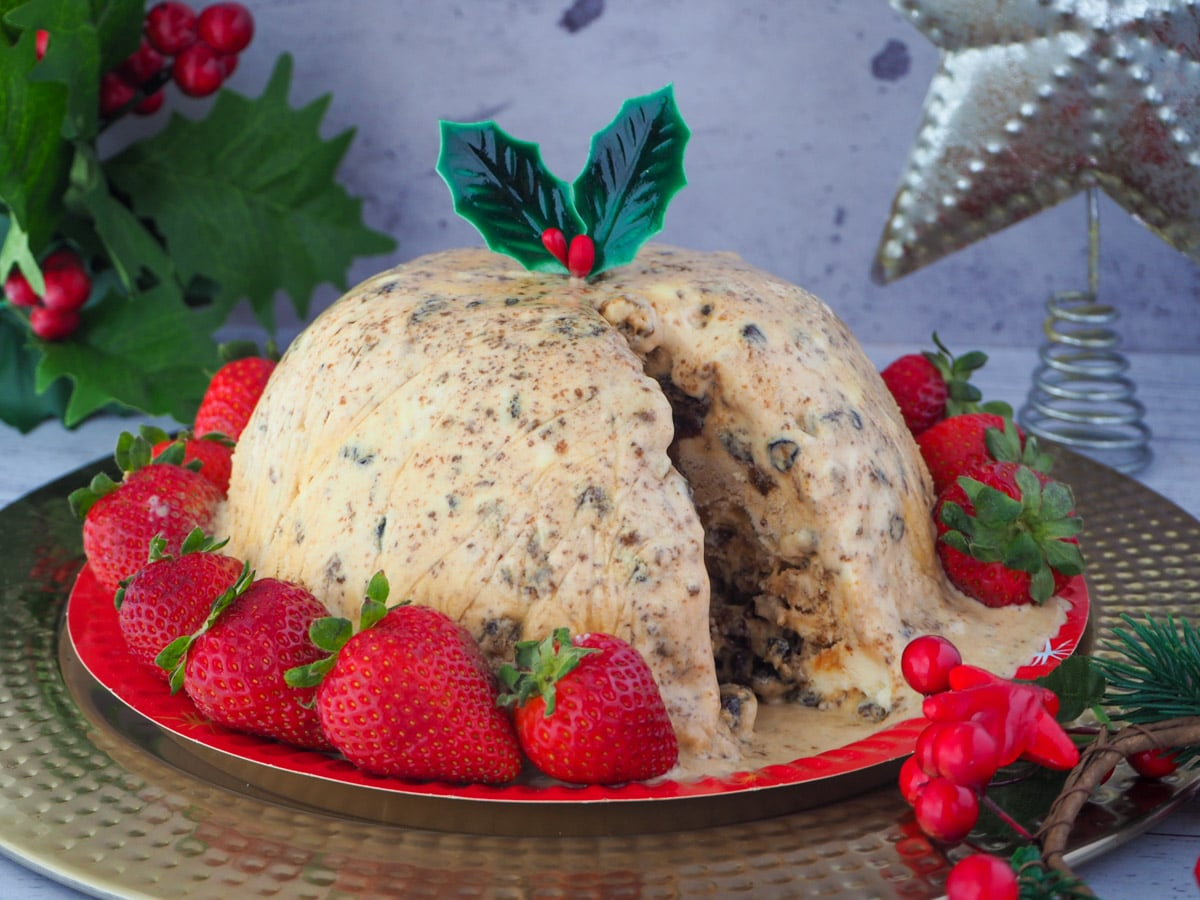 Christmas pudding ice cream a serve cut out, with holly garnish, surrounded by fresh strawberries, with holly and a Christmas star in the background