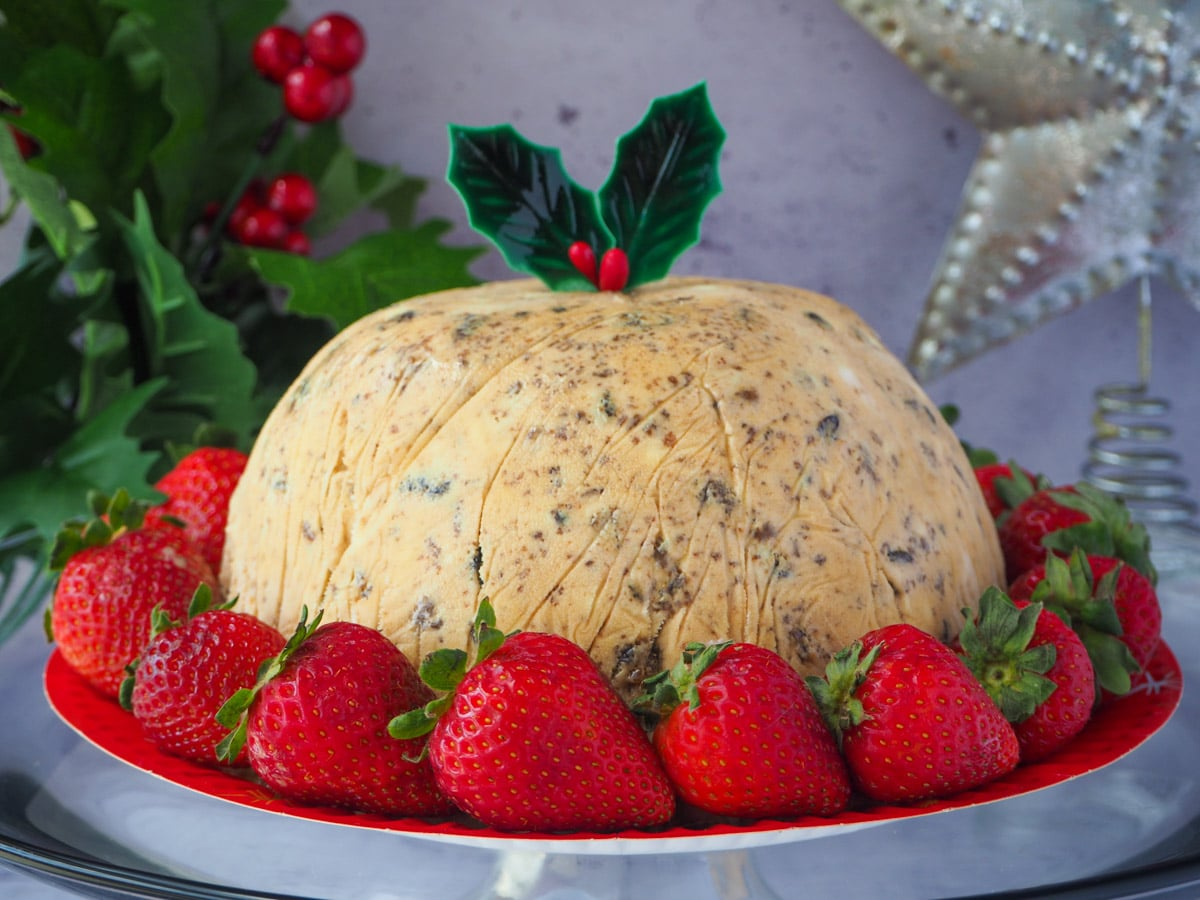 Christmas pudding ice cream with holly garnish, surrounded by fresh strawberries, with holly and a Christmas star in the background