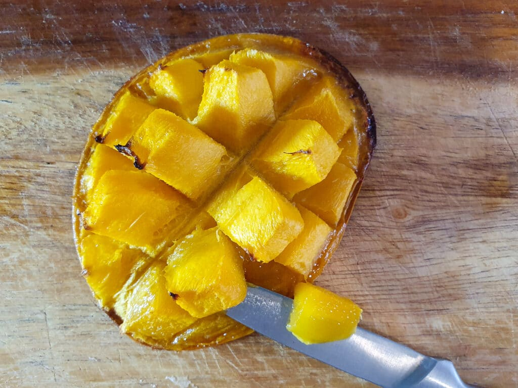 Cutting cooked mango flesh off mango skin.