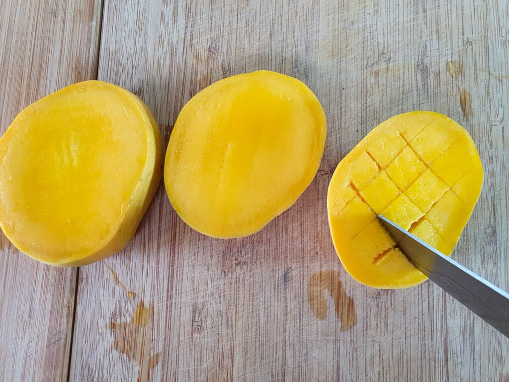 Slicing off mango cheeks and slicing into grid pattern without slicing through skin below, ready to pop out and baking on baking trays.