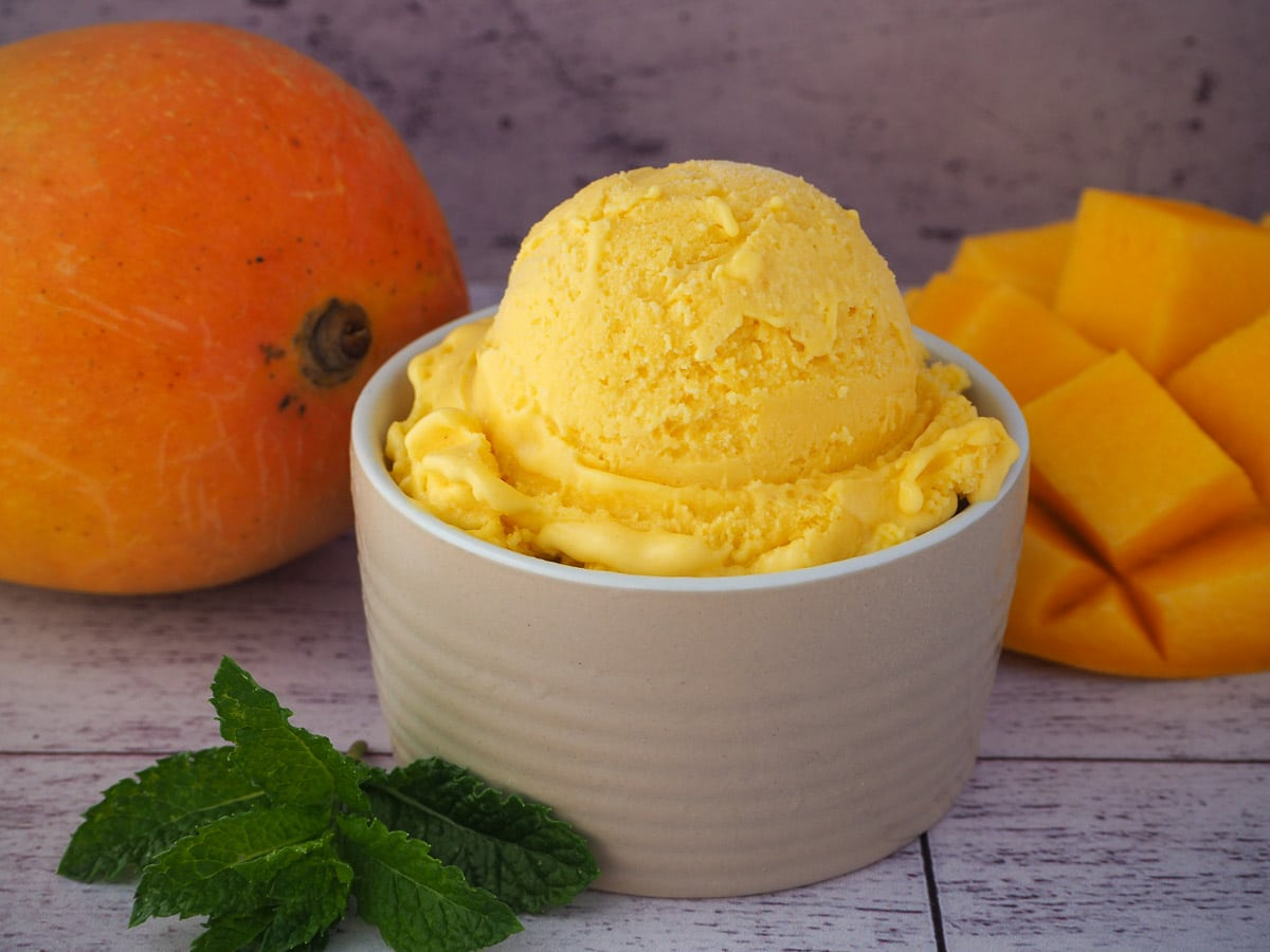 Mango ice cream in a small bowl, with fresh mint on the side and fresh mangoes in the background.