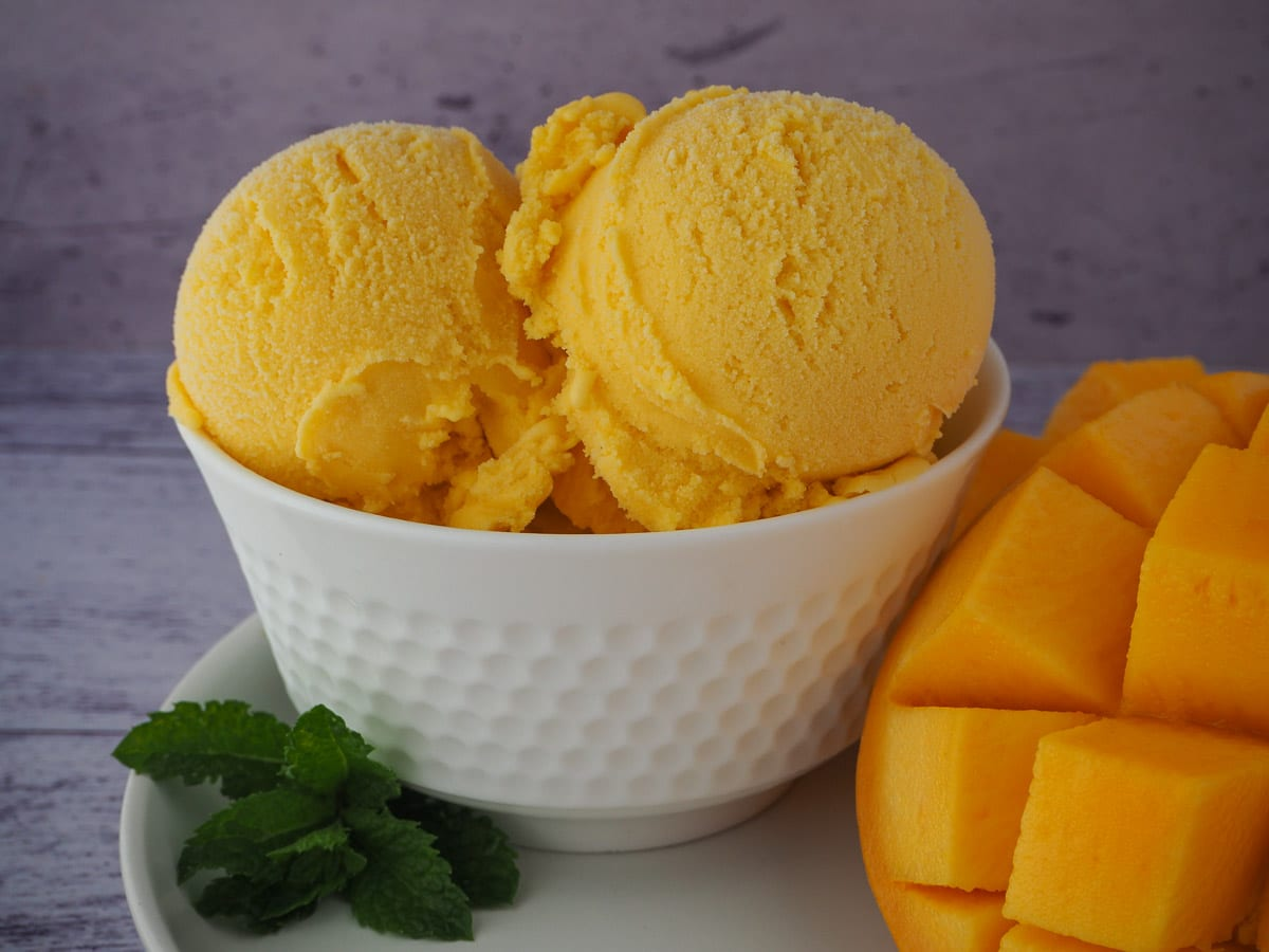 Scoops of mango ice cream in a white bowl, on a white plate with a spring of fresh mint and fresh mango.