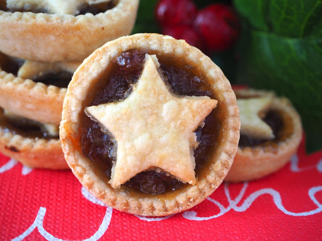 Mincemeat tart propped against a stack of mincemeat tarts, with holly in the background.