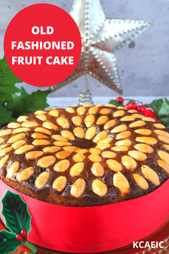 Old fashioned fruit cake decorated with almonds, with a red ribbon wrapped around it, on a gold plate, with holly decorations and a Christmas star in the background and text overlay, old fashioned fruit cake and KCAEIC.