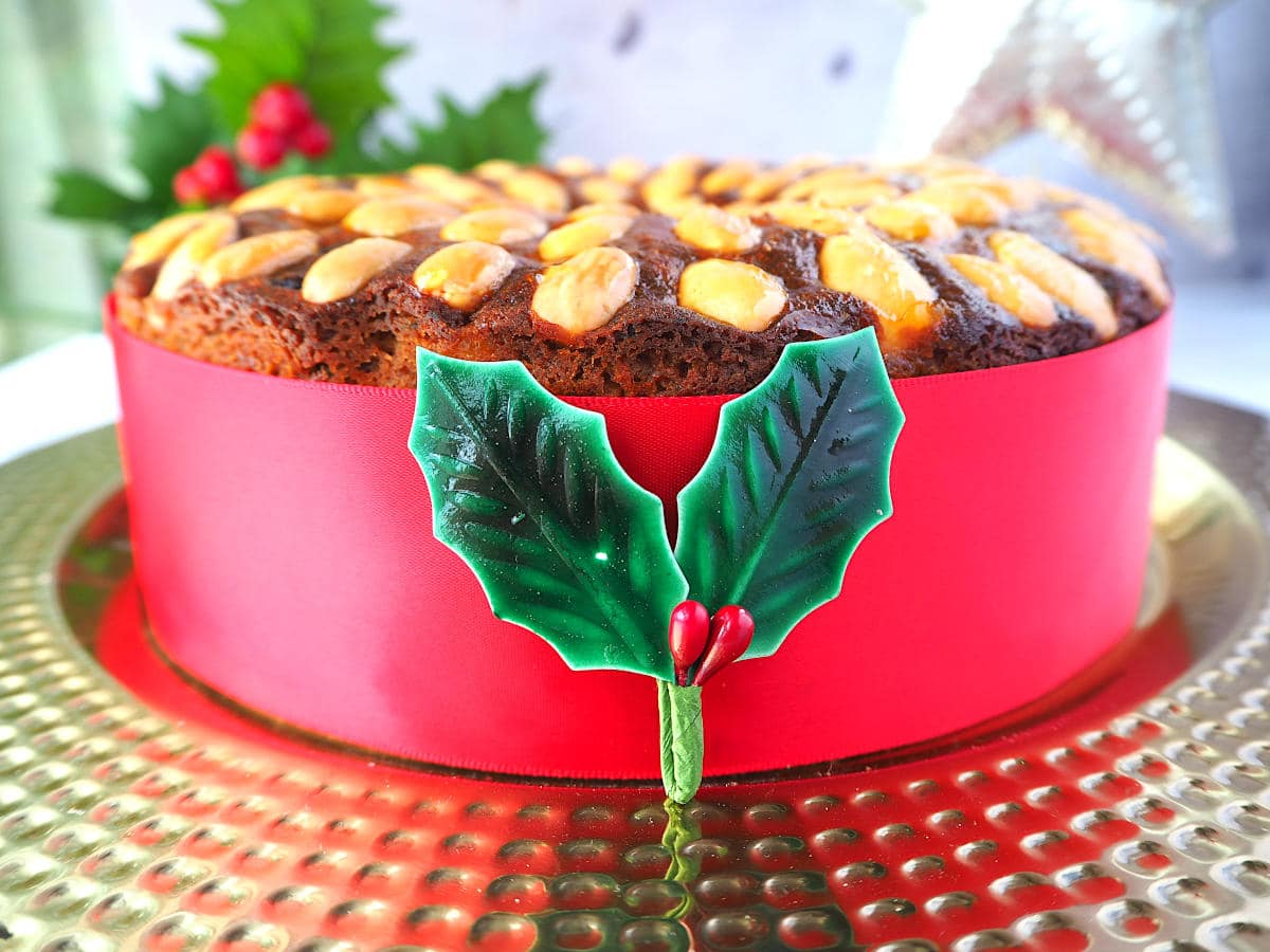 Old fashioned fruit cake decorated with almonds, with a red ribbon wrapped around it, on a gold plate, with holly decorations and a Christmas star in the background.