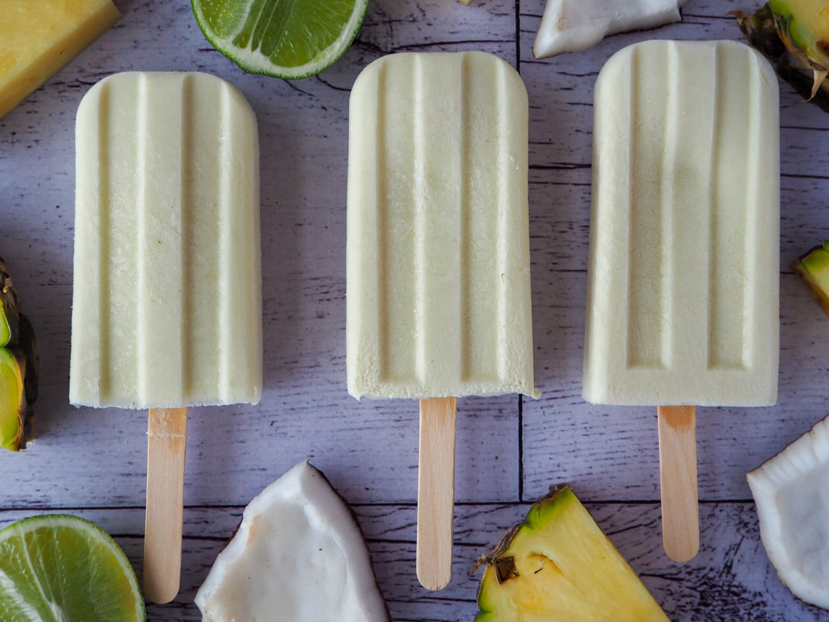 Row of three pina colada popsicles surrounded by fresh pineapple, coconut and limes.
