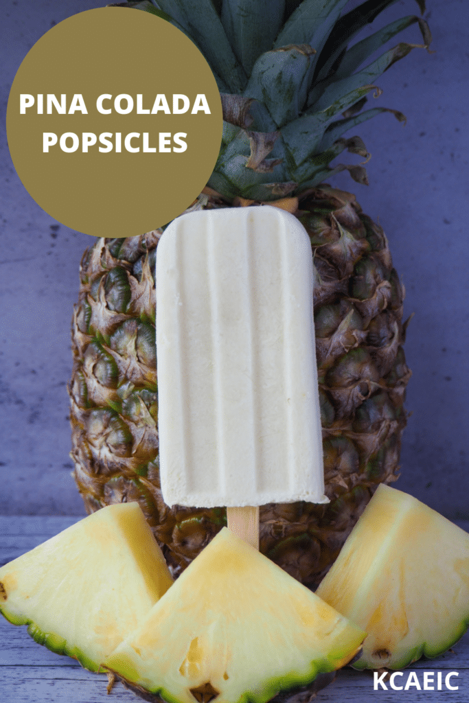 Single pina colada popsicle in front of a fresh pineapple, with fresh sliced pineapple in front and text overlay, pina colada popsicles and KCAEIC.