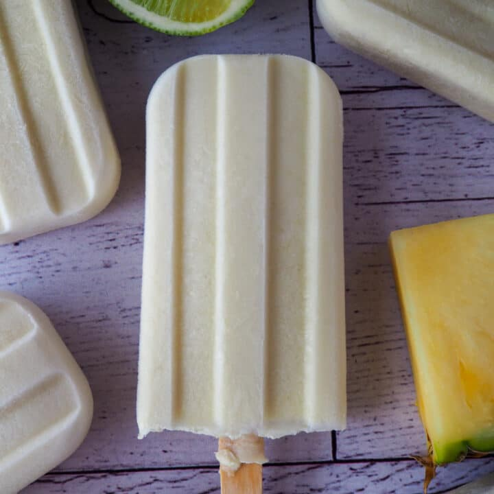 Close up of single pino colada popsicle, surrounded by other popsicles and fresh pineapple and lime.
