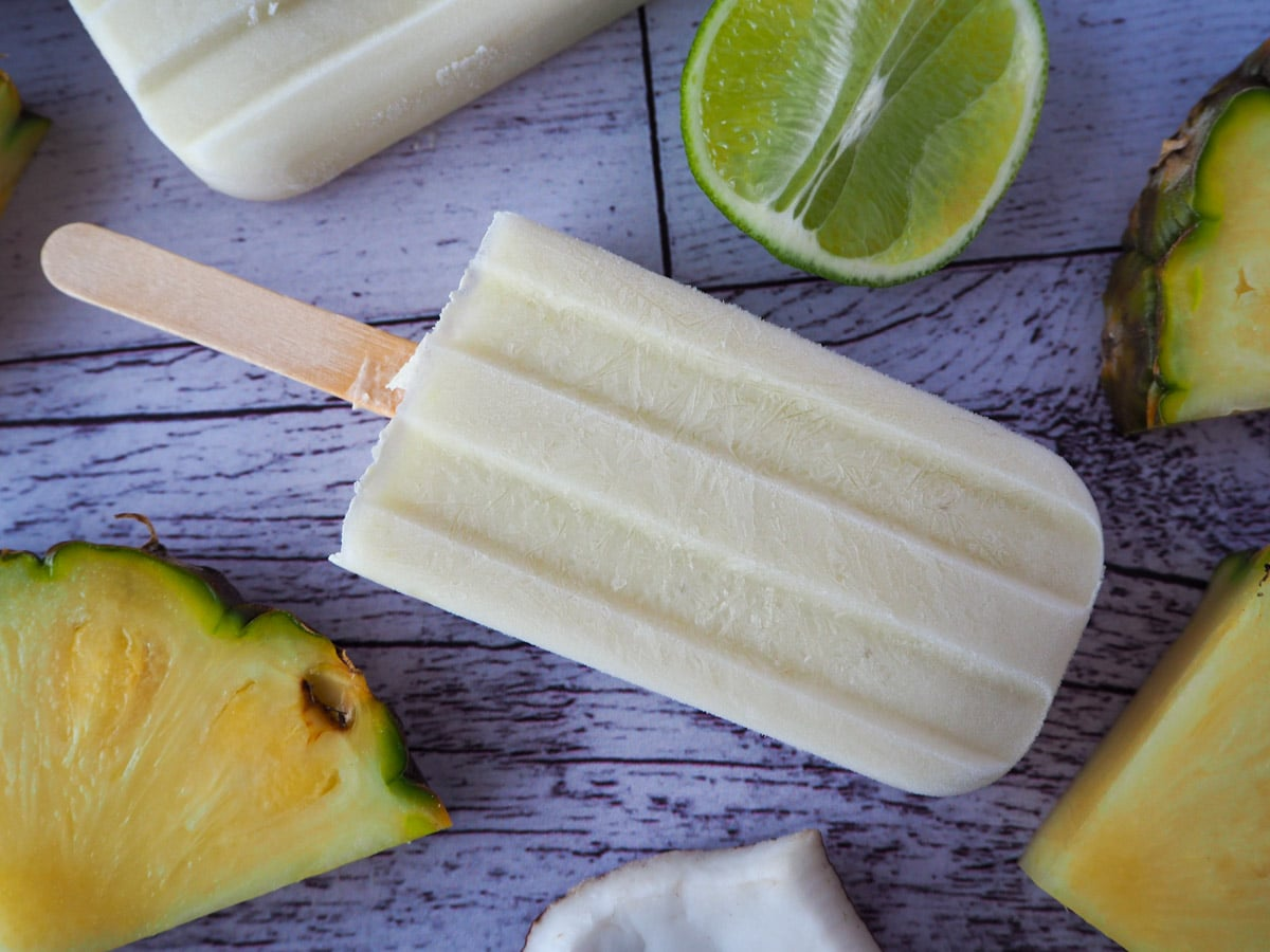 Close up of single pina cola popsicle on a diagonal, with fresh pineapple, coconut and lime around it.
