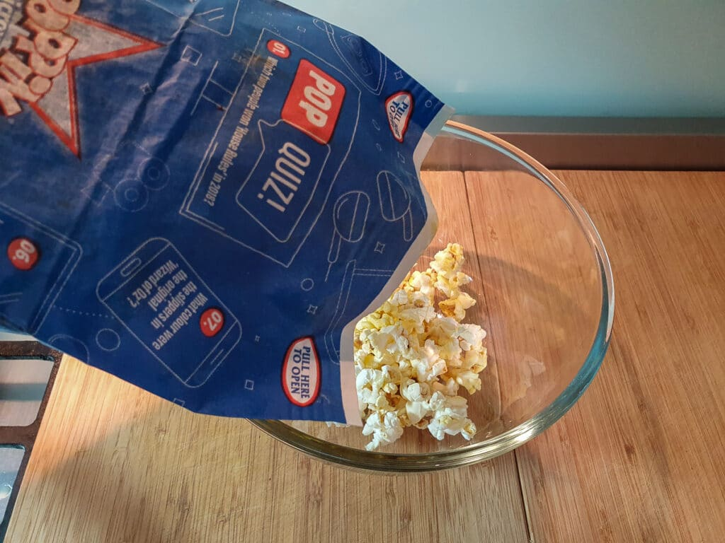 Tipping microwave popcorn into a bowl.