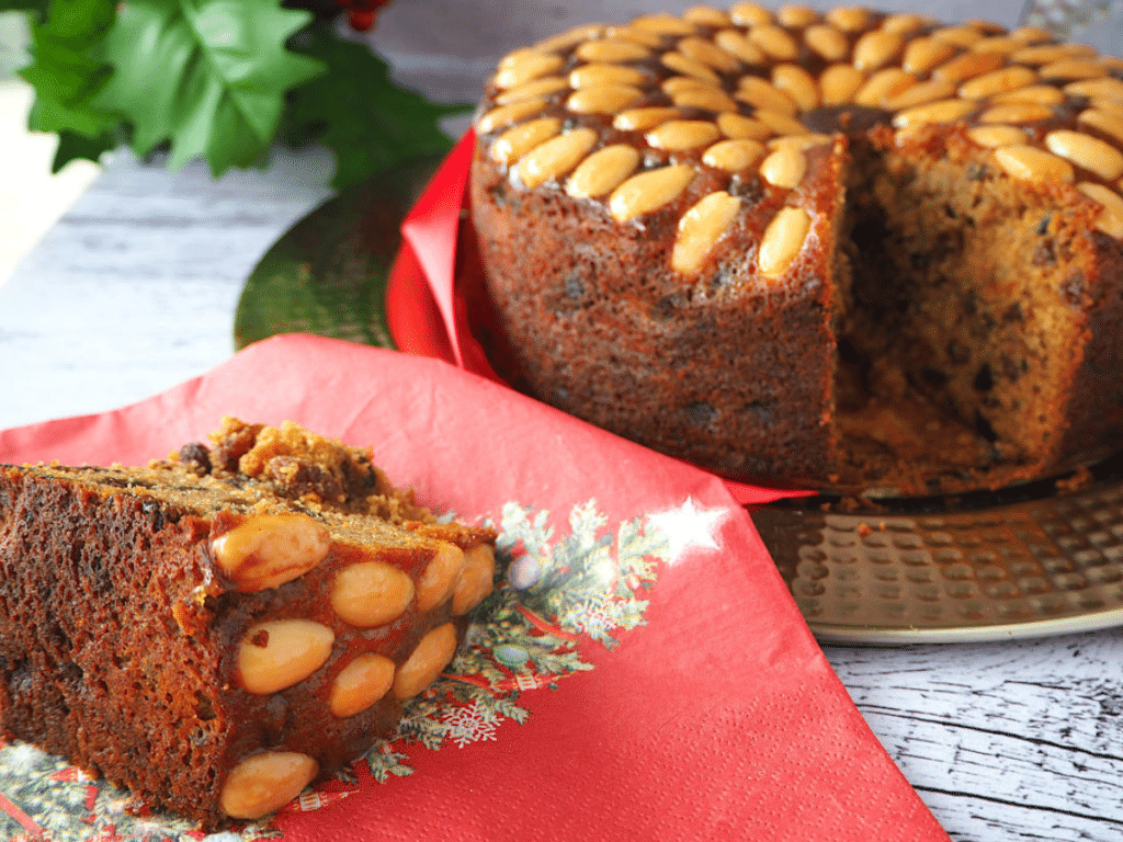 Slice of old fashioned fruit cake, on a Christmas serviette, with holly and cut cake in the background.