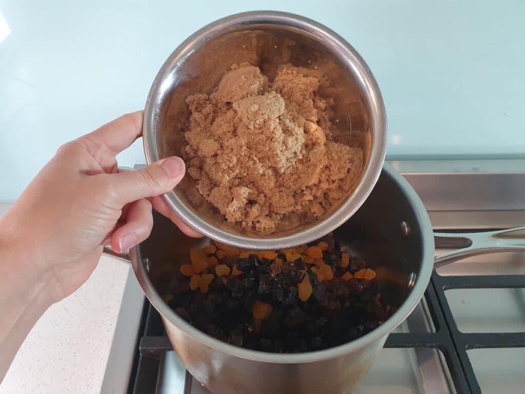 adding brown sugar to pot on stove.