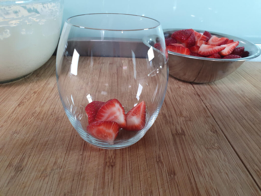 adding first layer strawberries to glass.