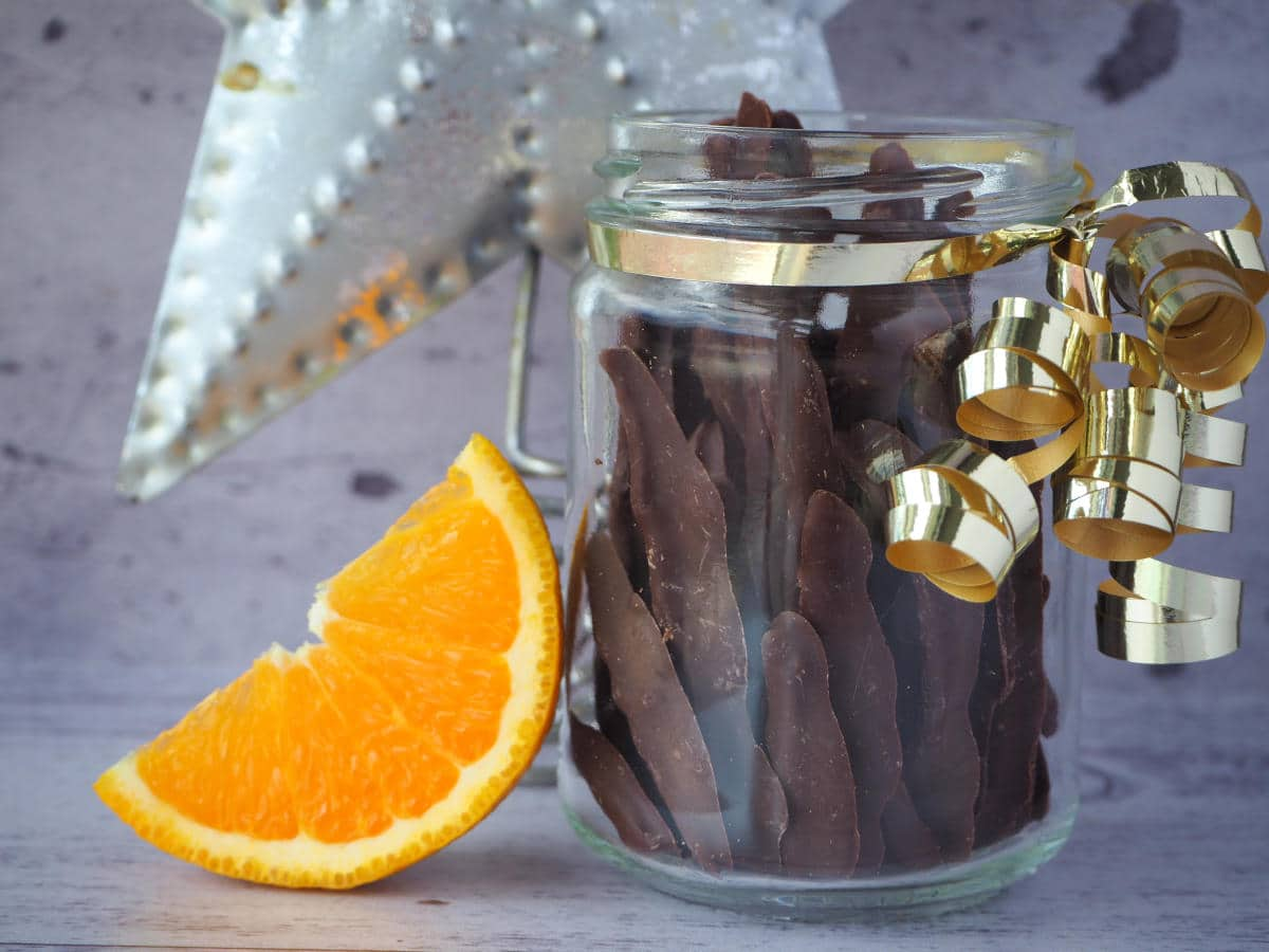 Glass jar of chocolate covered orange peel, with gold ribbon wrapped around it, slice of fresh orange leading against jar and Christmas star in background.