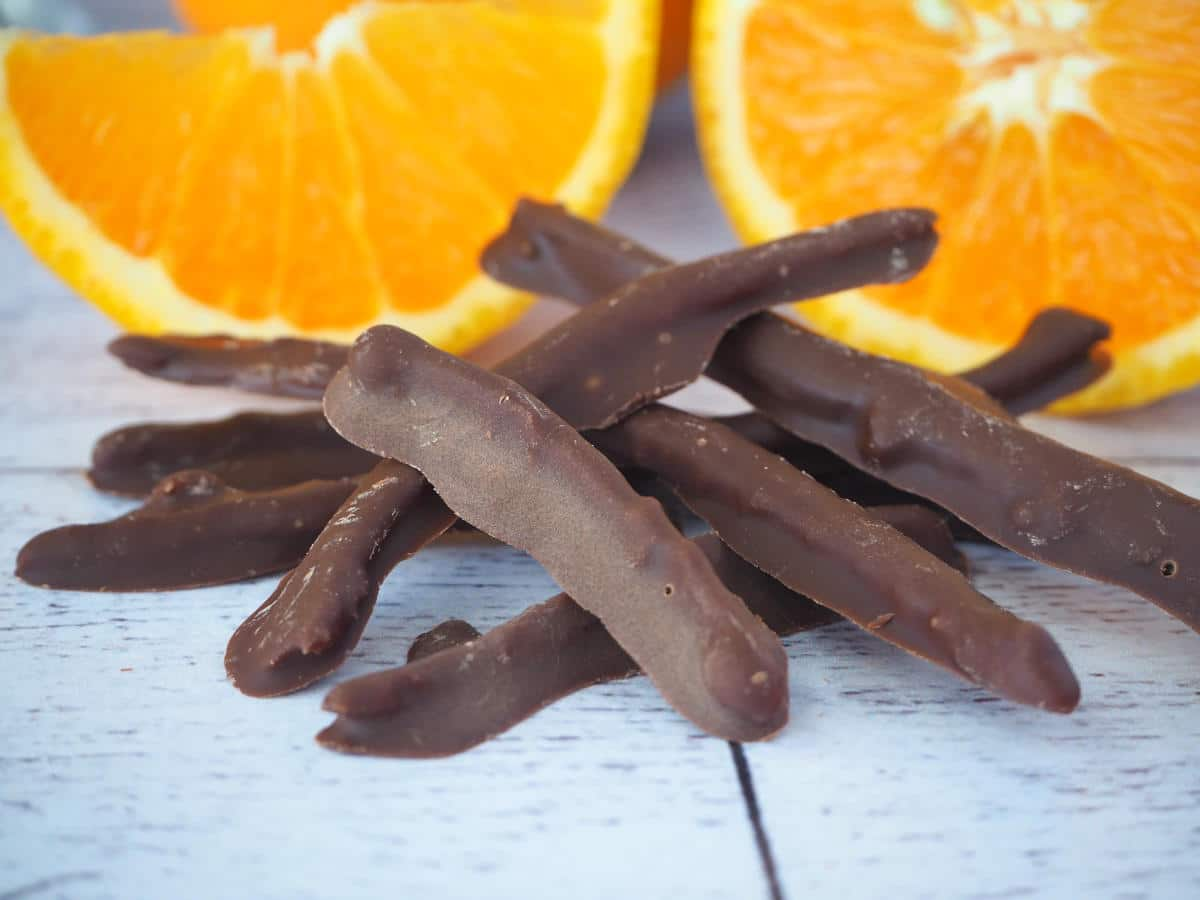 Chocolate covered orange peel with fresh slices of orange in background.