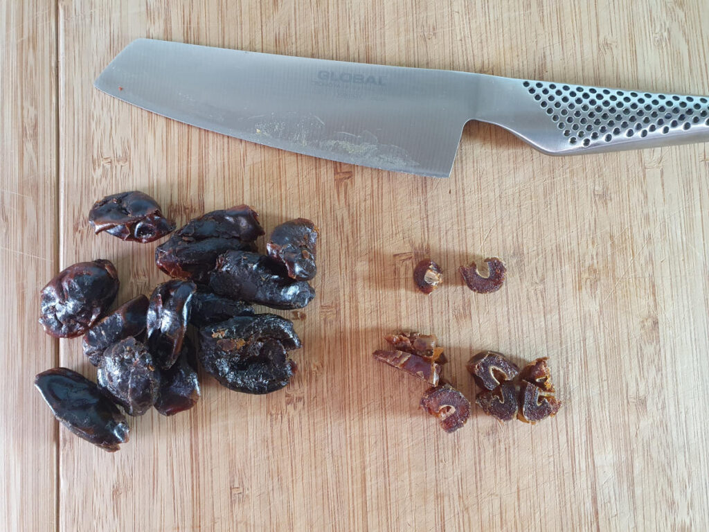 chopping pitted dates into small pieces.