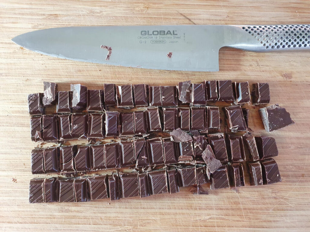 chopping up chocolate with a sharp knife.