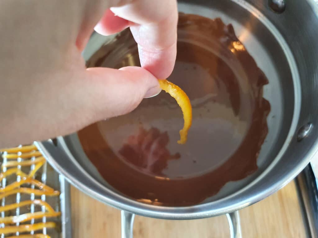 dropping one piece of candied orange peel into melted chocolate.