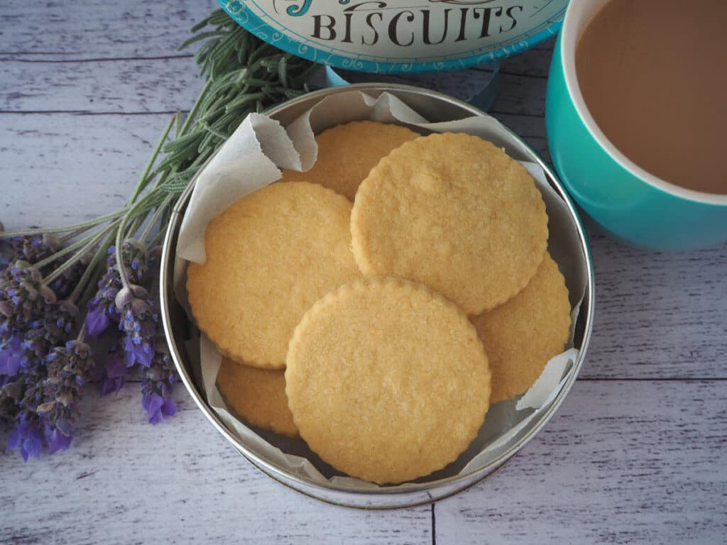 top down view gluten free shortbread in a biscuit tin, with a cup of tea and fresh lavender on the side.