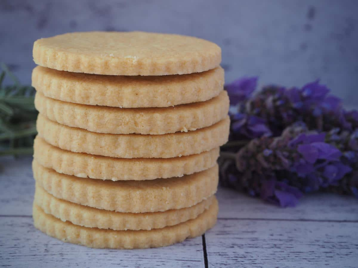 side view of stack of gluten free short bread with fresh lavender behind it.